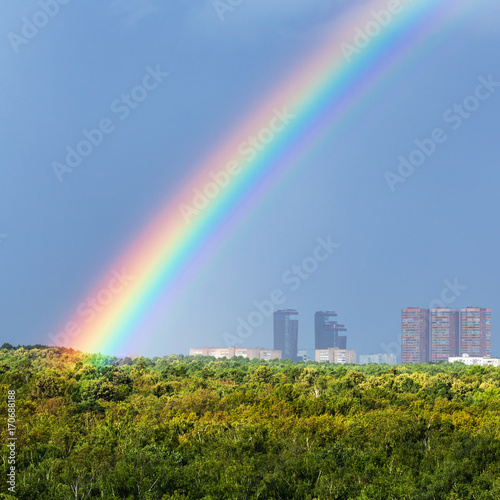 Papiers peints Moscou rainbow in blue sky over city and green trees