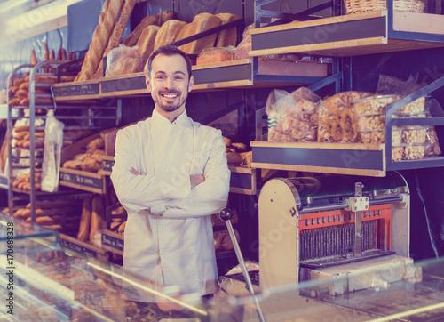 Man seller displaying assortment of bakery