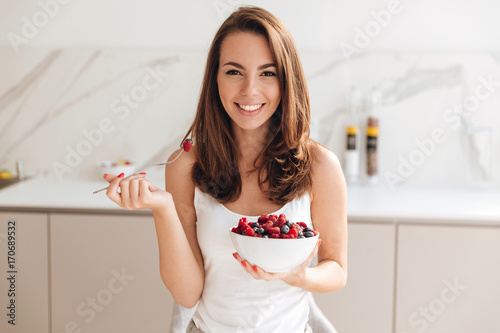 Happy smiling woman holding bowl with fresh berries