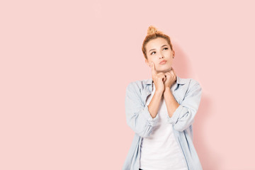 Young blonde girl with a wondering look on pink background