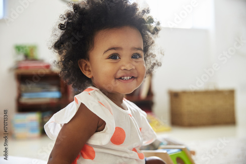 Happy Baby Girl Playing With Toys In Playroom