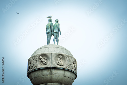 statue of boy and girl with a bird seen from the back in Oslo, Norway  Poster