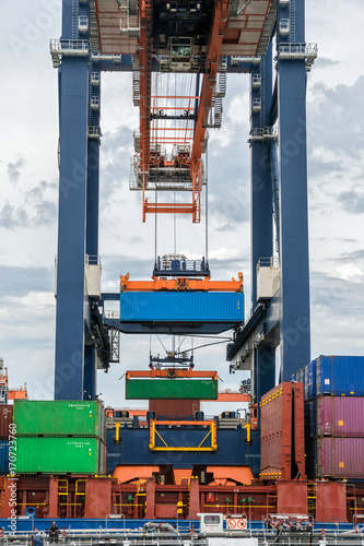 Aluminium Rotterdam Container ship being loaded with a sea container by gantry crane in the Port of Rotterdam.