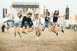 Friends jumping together on music festival