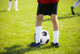 Close up legs and feet of football player in rwhite socks and black shoes playing with typical ball standing on green grass pitch outdoors. Child plays soccer training match