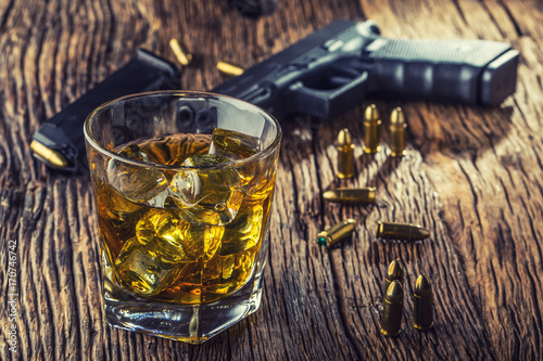 Gun and alcohol. 9mm pistol gun and cup whiskey cognac or brandy