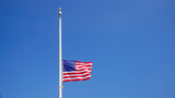 American Flag at Half Mast aka Half Staff Against Clear Blue Sky - 170753979