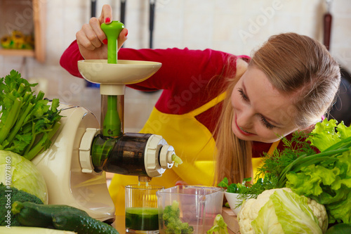 Foto op Plexiglas Sap Woman in kitchen making vegetable smoothie juice