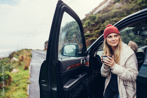 Woman having coffee during road trip - 170791995