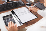 Businessperson's Hand Calculating Invoice - 170792104