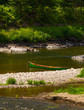 Green squareback canoe at the shore of a mountain stream in Gaspe, Quebec