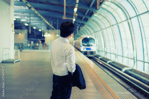 Asian young businessman waiting metro train at train station. Business travel concept.