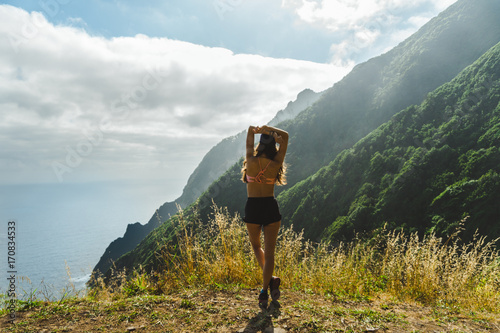 Papiers peints Vieux rose Adventurer girl looking at Madeira volcano mountain range and ocean in the morning