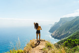 Hiker girl standing at rocks and overlooking Madeira volcano coast and ocean - 170834933