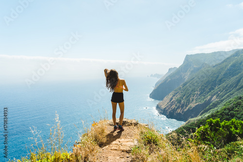 Wall mural Hiker girl standing at rocks and overlooking Madeira volcano coast and ocean