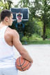 Young athletic man playing basketball in a beautiful park surrounded with trees.