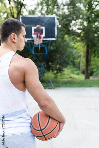 Fotobehang Basketbal Young athletic man playing basketball in a beautiful park surrounded with trees.