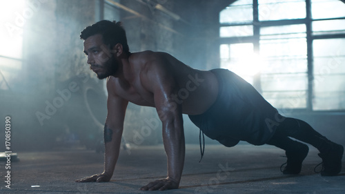 Muscular Shirtless Man Covered in Sweat Does Push-ups in a Deserted Factory Remodeled into Gym. Part of His Cross Fitness Workout/ High-Intensity Interval Training.