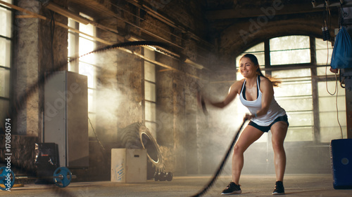 Athletic Female in a Gym Exercises with Battle Ropes During Her Cross Fitness Workout/ High-Intensity Interval Training. She's Muscular and Sweaty, Gym is in Deserted Factory.