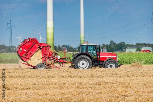 Fotobehang Trekker Traktor mit Rundballenpresse auf dem Feld - 0259