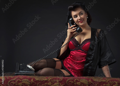 Beautiful woman speaking via vintage phone.