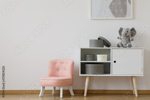 Pink chair next to white shelf