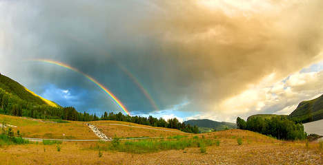 Double rainbow over green forest in summer