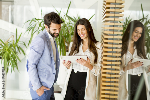 Wall mural Young business couple using tablet in the office