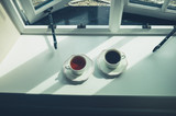 Cup of coffee and tea by the window