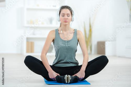 Fototapeta young woman doing yoga on mat at home