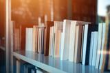 Fototapety Books on library shelf through window