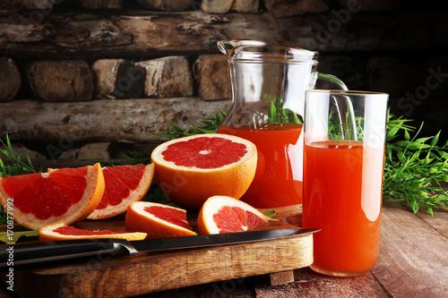 Fotobehang Sap Grapefruit juice and ripe grapefruits on a wooden background