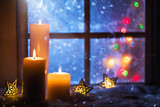 Winter decoration with candles near the snow-covered window