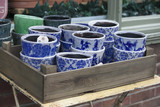 flower pots with blue ornament for sale at the entrance to the flower shop