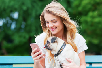 young woman with a pug handles a phone