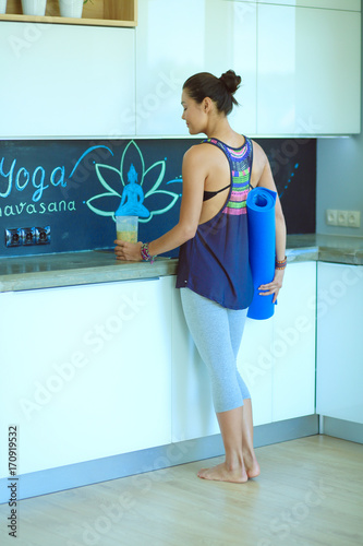 Fotobehang School de yoga Portrait of smiling woman holding in her hand a yoga mat while standing at studio. Yoga. Woman. Wellness