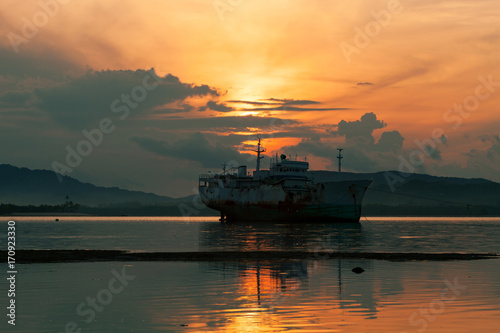 Fotobehang Thailand Old boat in the sea beautiful sunrise at phuket thailand.