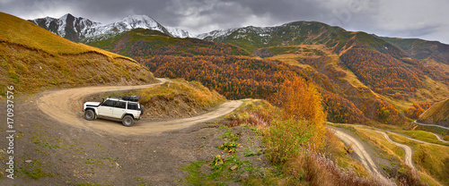 Aluminium Zomer mountain serpentine in the autumn mountains, bright autumn colors, in the background the peaks covered with snow