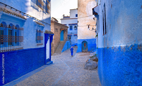 Fotobehang Marokko A Moroccan woman in national clothes is walking down the street of the city