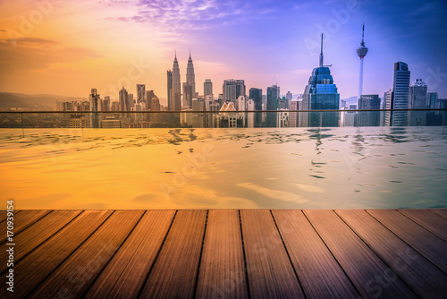 Cityscape of Kuala lumpur city skyline with swimming pool on the roof top of hotel and wooden floor at sunrise in Malaysia Poster