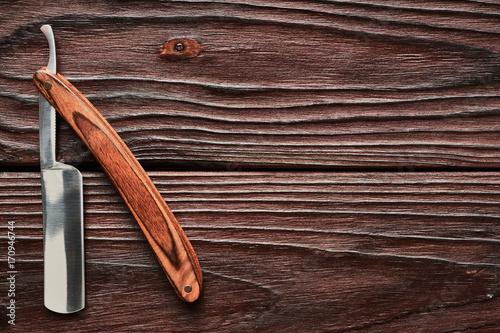Vintage barber shop straight razor tool on wooden background Poster