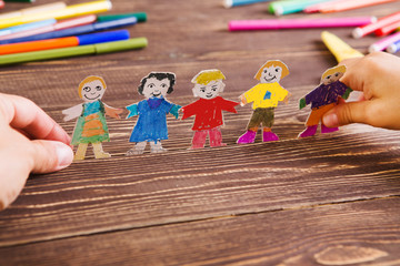 the child does figures of people of paper. Paper people on wooden background. Creative child play with craft..