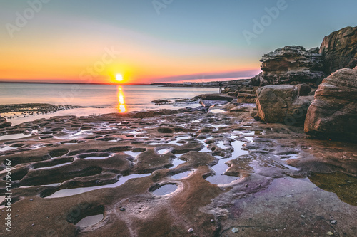 Aluminium Strand stunning sunset with rock pools in a secluded location