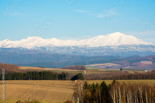 Fotobehang Pool 秋の丘陵畑作地帯と冠雪の山並み、大雪山