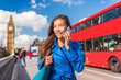 London city businesswoman calling on mobile phone app talking to cellphone on Westminster bridge with red bus and Big Ben, Parliament urban background. Europe destination, England, Great Britain.
