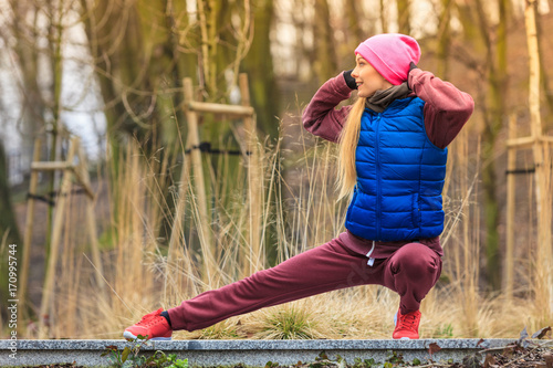 Wall mural Woman wearing sportswear exercising outside during autumn