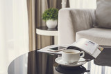 Cup of coffee on a round table with sofa in living room