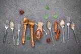 Desserts background and menu design. Metal utensils ,honey dipper ,star anise and cinnamon sticks  setup on dark stone background. - 171007567
