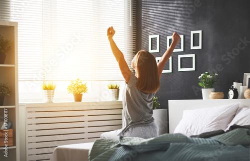 młoda kobieta obudziła się rano w sypialni przy oknie z plecami