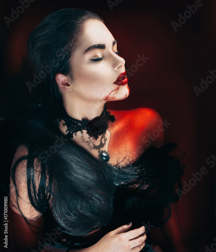 Beauty Halloween sexy vampire woman with dripping blood on her mouth